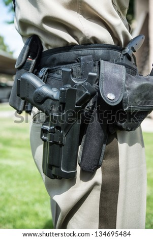The heavyweight, heavy duty tactical belt worn by today's police officers, including semiautomatic pistol. - stock photo