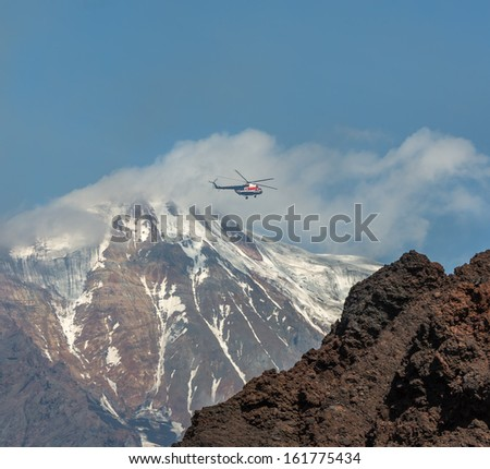 The helicopter flies to the plateau on the background of the volcano Ostry Tolbachik - Kamchatka, Russia