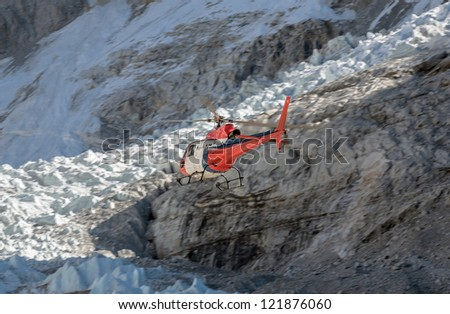 The helicopter on the background of the Khumbu glacier near EBC - Everest region. Nepal - stock photo