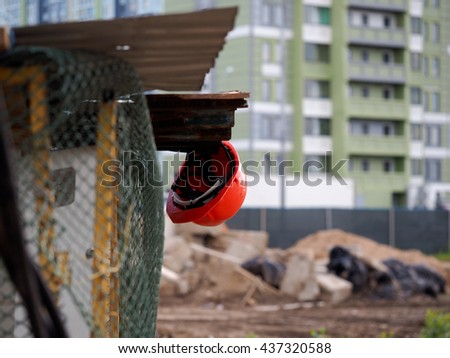 The helmet is against the background of a construction site. Completed new homes. Metal mesh fence - the fence construction - stock photo