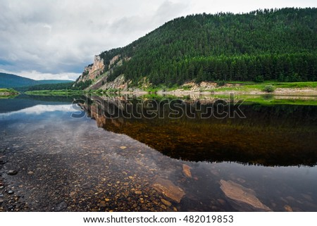 The high river bank reflected in water of the river, Sakha (Yakutia) Republic, Eastern Siberia, Russia