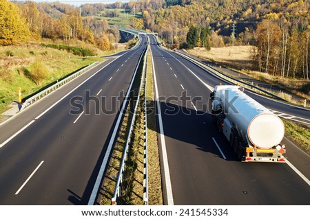 The highway between deciduous trees in autumn colors, in the foreground riding a white tank, in the distance electronic toll gates and cars, view from above - stock photo