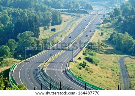The highway between forests in the landscape, on the highway electronic toll gate, in the distance on the highway cars and bridges, view from above - stock photo