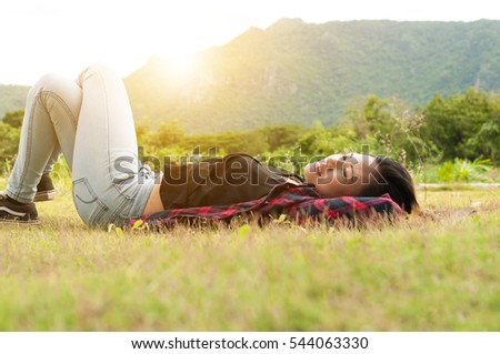 The hipster beautiful happy young woman lies in the field on morning time.relax time in holiday