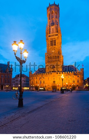 The historic belfry and city center square in the old medieval old town of Bruges (Brugge), Belgium at blue hour - stock photo