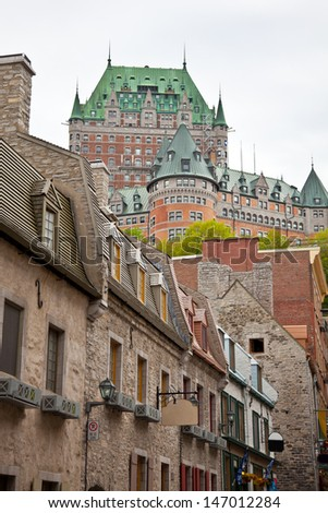 The historic Chateau Frontenac towers behind other old historic buildings in Lower Quebec City. - stock photo