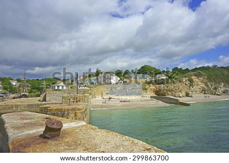 The Historic Cornish fishing Harbour of Charlestown in Cornwall under a cloudy blue sky with tall ships and people on the beach in summer time, some scenes from TV series Poldark were filmed here, UK - stock photo