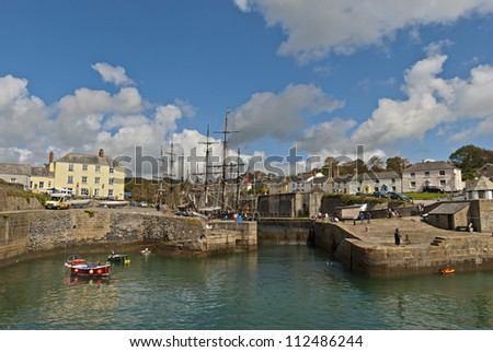 The Historic Harbour of Charlestown in Cornwall under a blue sky with tall ships - stock photo