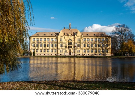 The historic high school building built in 1901 in Litovel, in the mirror of pond by autumn, Czech Republic - stock photo