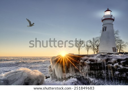 The historic Marblehead Lighthouse in Northwest Ohio sits along the rocky shores of the frozen Lake Erie. Seen here in winter with a colorful sunrise and snow and ice.