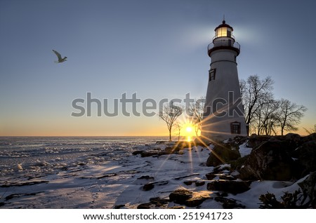 The historic Marblehead Lighthouse in Northwest Ohio sits along the rocky shores of the frozen Lake Erie. Seen here in winter with a colorful sunrise, snow on the ground and a seagull flying by.