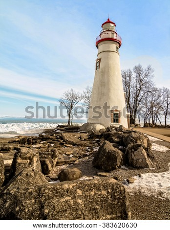 The historic Marblehead Lighthouse in Northwest Ohio sits along the rocky shores of the frozen Lake Erie. Seen here in winter with a colorful sky and some snow on the ground. - stock photo