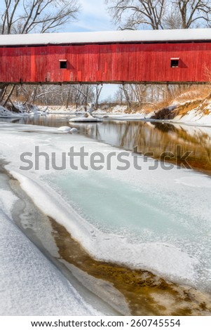 The historic red Oakalla Covered Bridge crosses a snowy and partially frozen Big Walnut Creek in rural Putnam County Indiana . - stock photo