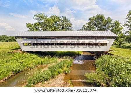 The historic white Hannaway Covered Bridge crosses Clear Creek, near Clearport in Fairfield County, Ohio. - stock photo
