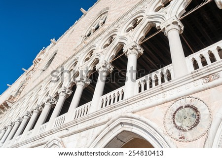 The historical Doge's Palace facade arches detail on sunny clear blue sky, Venice, Italy