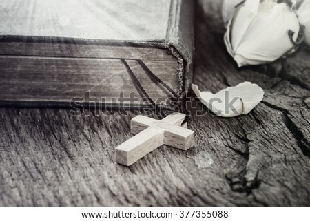 The Holy Bible and a crucifix on the wooden table. - stock photo