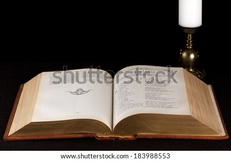 The Holy Bible, candle and candlestick on black background.