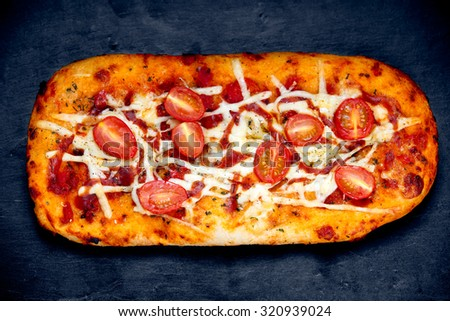 The Homemade Pizza. made with fresh plumb tomatoes, tomato sauce, mozzarella, cheddar and herbs leaves. background , texture. - stock photo