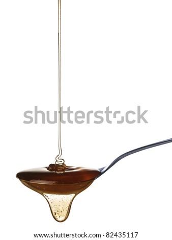 The honey slowly falls onto the spoon. - stock photo