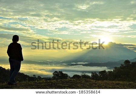 The hopeful Sunrise. Silhouette of a person looking at the sunrises from behind the mountain.   - stock photo