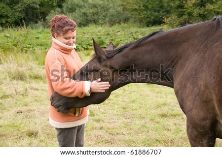 The horse looks in his jacket pocket. Woman pets brown horse. - stock photo