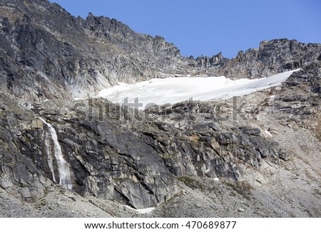The hostile Devil's Punchbowl landscape with a waterfall 3700 feet (1130 meters) above sea level (Skagway, Alaska).