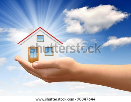 The house in  hands on blue sky - stock photo