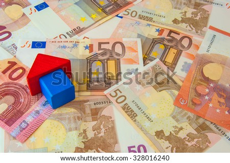 The house made from wooden toy blocks with euro money.