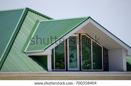 the house with plastic windows and a green roof of corrugated sheet roofing of metal