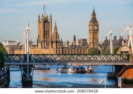 The Houses of Parliament seen through the Hungerford Bridge and Golden Jubilee Bridges in London - stock photo