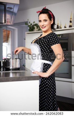 the housewife in pin up style cooking meal. She wearing dress with pinafore