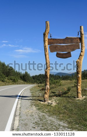 The huge blank wooden sign by the highway. Clear skies and sunny day on the hills. - stock photo