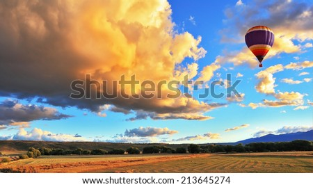 The huge rain cloud lit orange sunset. In the sky flying multicolored balloon - stock photo