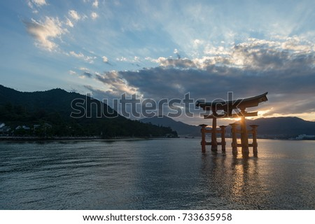 The huge Shinto Torii gate of the Itsukushima Shrine stands in the Seto Inland Sea of Japan, seen here at sunset