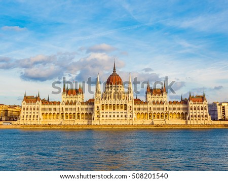 The Hungarian Parliament Building on the bank of the Danube river covers by yellow sunlight in Budapest, Hungary