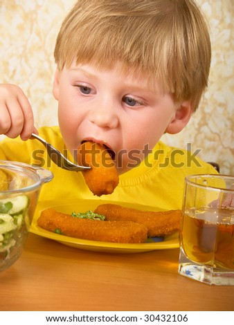 The hungry little boy eats meat - stock photo