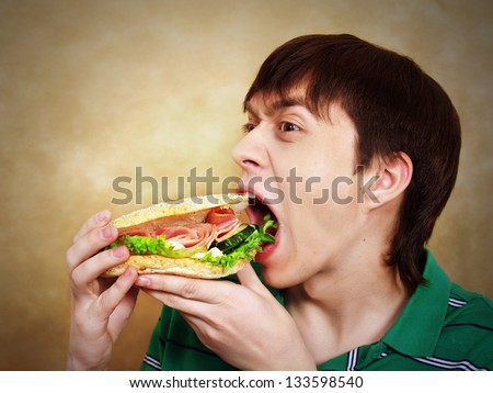 The hungry young man aggressively eats a hamburger. Fast food