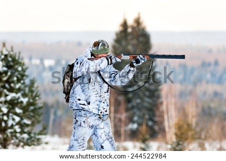 the hunter in the winter camouflage shooting from a gun - stock photo