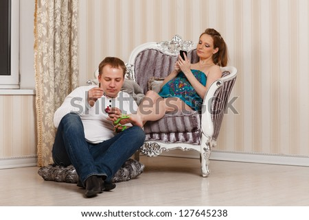 The husband does a pedicure to the pregnant wife of the house. Happy pregnant family. - stock photo