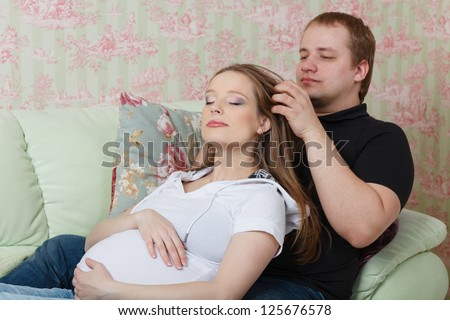 The husband does massage of a head of the pregnant wife, sitting on a house sofa. - stock photo