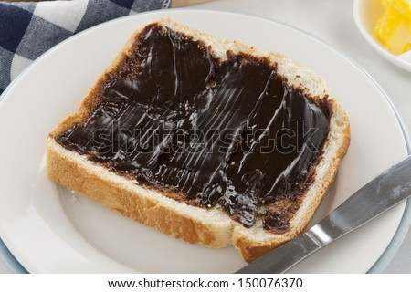 The iconic Australian spread vegemite on a slice of fresh bread.