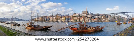 The iconic Rabelo Boats, the traditional Port Wine transports, with the Ribeira District and the Dom Luis I Bridge over the Douro River. Porto, Portugal. Unesco World Heritage. - stock photo