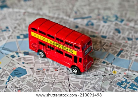 The iconic red bus miniature on the map of London - stock photo