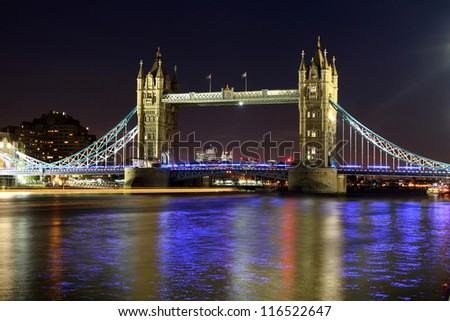 The iconic Tower Bridge of London lit up at night over the River Thames