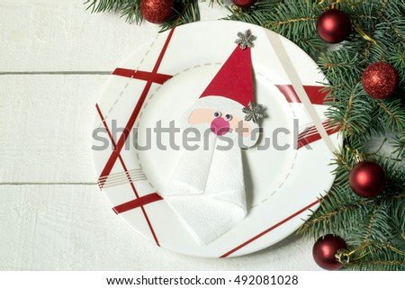 The idea of Christmas decoration for the table setting. Homemade decor for serviette in form of Santa Claus on a plate. Decorated Christmas tree branch on a white wooden table