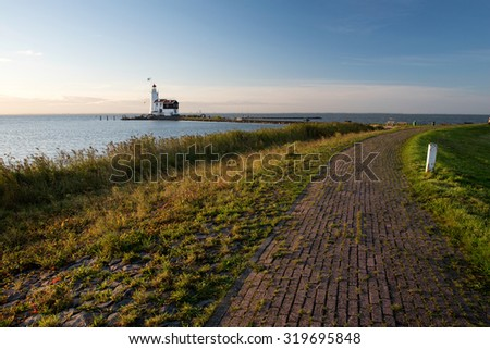 The idyllic lighthouse of Marken at sunrise, seen from the dike protecting the village of Marken from the water - stock photo