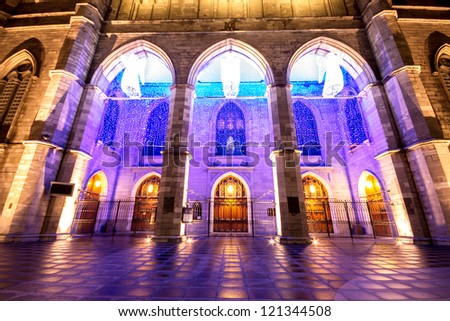 The illuminated Facade of the Notre-Dame Basilica in Montreal with three angels above the doors as Christmas decoration - stock photo