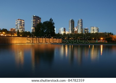 The illuminated skyline of Bellevue, Washington at twilight reflected in a pool at Downtown Park.