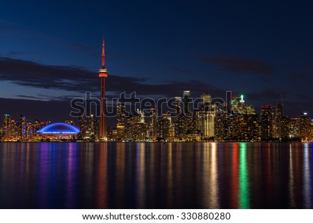 The illuminated Toronto skyline with Lake Ontario in the foreground, as seen from Center Island. - stock photo