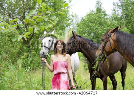 The image of a beautiful brunette girl with horses